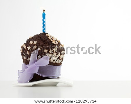 single chocolate muffin on white plate, decorated with white sugar stars, wrapped in purple ribbon and bow, with blue candle on top, on white background - stock photo