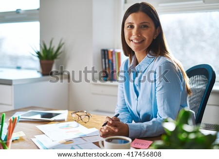 Single confident smiling woman in blue shirt with folded hands at desk in a bright, sunlight filled professional home office