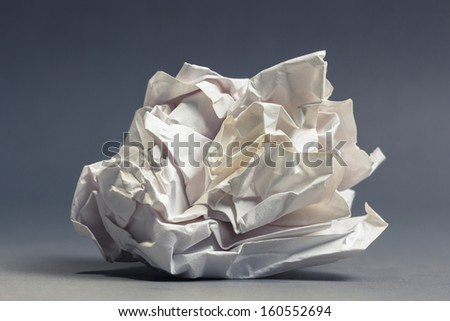 Single crumble paper ball on gray ground - stock photo