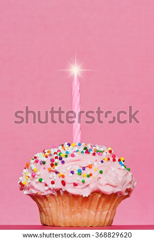 Single cupcake decorated with pink frosting and a single pink candle with a star burst on a pink background