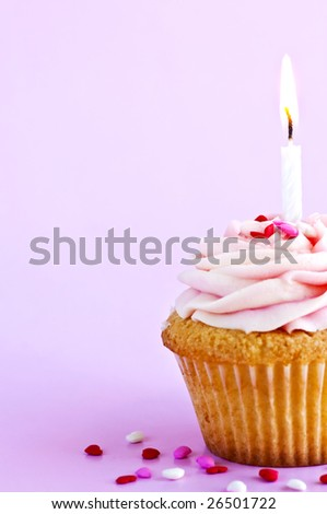 Single cupcake with icing sprinkles and candle - stock photo
