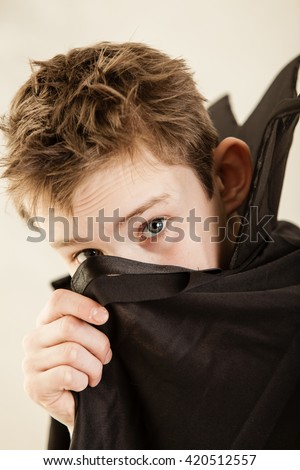Single cute little boy dressed in black vampire cloak using hand to cover part of his face over white background