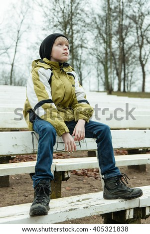 Single daydreaming child wearing winter coat, black hat, blue jeans and boots sitting on old white wooden bench looking upwards with snow and bare trees behind him - stock photo