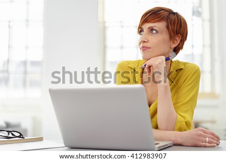 Single daydreaming woman in yellow blouse with pen in hand near chin looking up from laptop in small office with bright windows