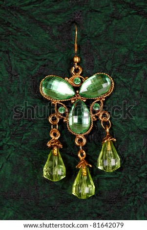 Single earring on textured green background. - stock photo