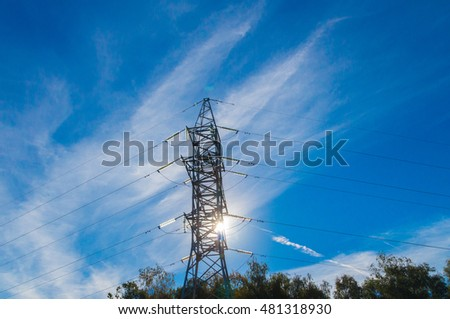 Single electric pylon of transmission line against shining sun and serene blue sky. Pictorial clouds drawn by wind. Luminous glass insulators.