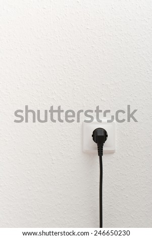 Single electric socket with plug on white wall - stock photo