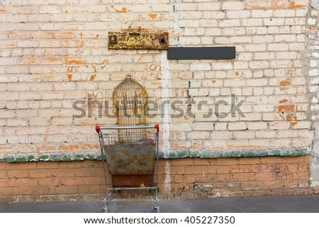 Single empty bird cage in old rusty shopping cart stuck inside painted brick wall with weather iron plates above it - stock photo