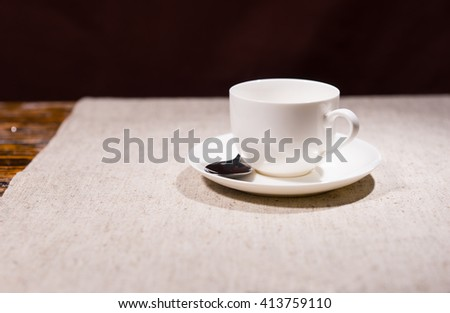 Single empty white ivory teacup and saucer with stainless steel spoon over gray cloth and part of wooden table in background - stock photo