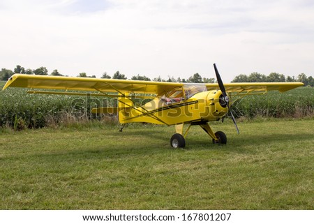 Single engine fixed wing aeroplane parked on a green grass field on display during a rural airshow