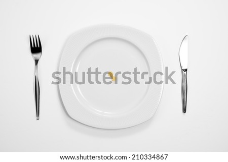 Single farfalle pasta on the middle of a plate, knife and fork.