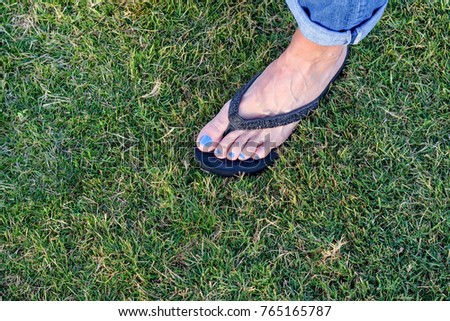 Single female foot in grass with room for copy text