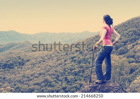 Single female hiker looks out at view in mountains with forest below her - stock photo