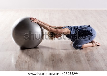 Single flexible woman stretching her shoulders with outstretched arms on top of silver fitness ball on hardwood studio floor