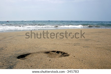 Single footprint shot from low angle on the beach