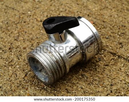 Single garden hose valve on wet concrete - stock photo