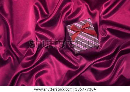 Single gift box with red bow on satin background - stock photo