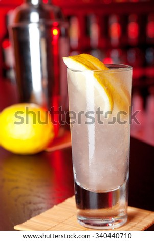 Single glass of Papa Doble cocktail at the bar, lit in red light. Shaker and lemon in background. Ingredients: 1 shot white rum 1 shot lime juice 1 shot grapefruit juice lemon slices to garnish - stock photo