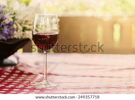 Single glass of red wine over natural background with hazy sunlight and bokeh. Copy space, selective focus, shallow Depth of field - stock photo