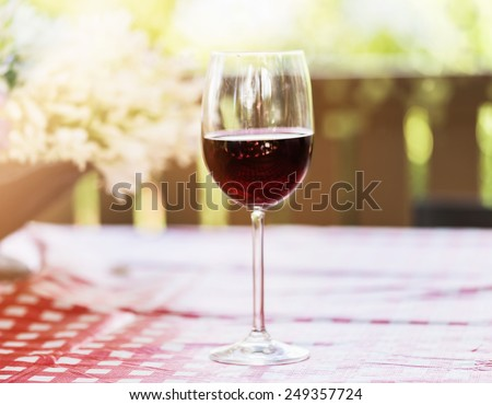Single glass of red wine over natural background with hazy sunlight and bokeh. Selective focus, shallow Depth of field - stock photo