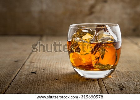 Single glass of whisky bourbon on the rocks golden on old rustic wooden surface open space - stock photo