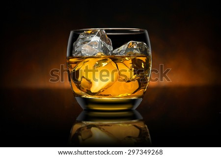 Single glass of whisky whiskey bourbon on ice with a reflective black surface and wooden background - stock photo