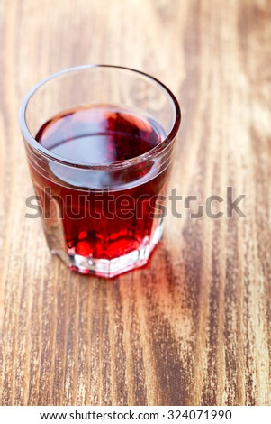 Single glass with red drink - stock photo