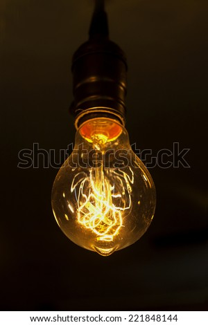 single glowing round bulb tungsten lamp, heated filament light, incandescent illumination on dark background - stock photo