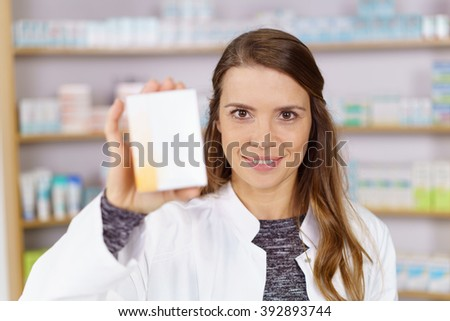 Single grinning pharmacist with white lab coat and long hair holding up an obscured box of medicine in pharmacy - stock photo