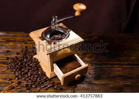 Single hand crank square shaped wooden coffee grinder with blank label and drawer full of grounds over table with dark background and scattered dark beans