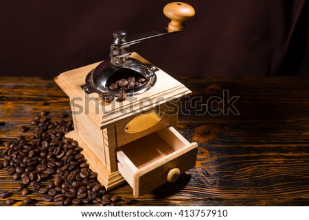 Single hand crank square shaped wooden coffee grinder with blank label and open drawer over table with dark background and scattered dark beans