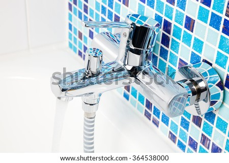 Single handle wall mount chrome bathroom faucet with running water on a blue mosaic wall - stock photo
