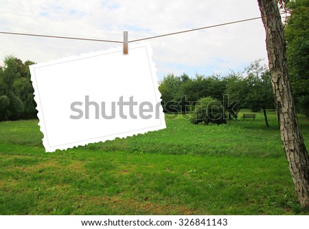 Single hanged postcard with clothespin on green park background