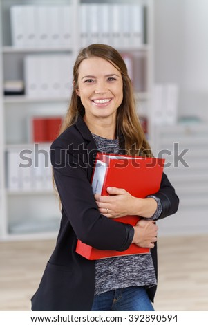 Single happy young executive with long brown hair and black jacket standing in small office holding red binder close to her chest