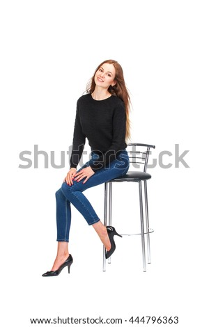 Single happy young woman sitting on a white chair in studio