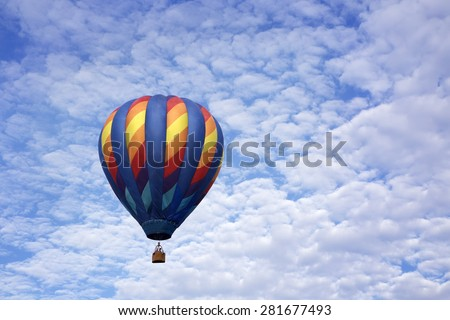 Single hot air balloon floating up into a blue sky full of white fluffy clouds