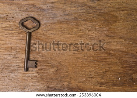 single key on a old wooden table - stock photo