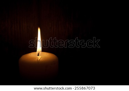 Single lit candle in the dark