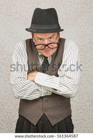 Single mad businessman with hat and folded arms