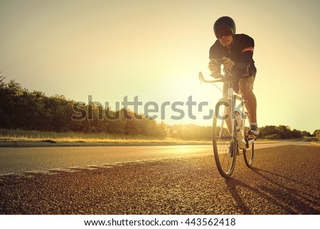 Single male bicyclist back lit by bright yellow sunlight while racing his bike on road bike at sunrise - stock photo