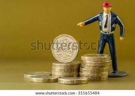 Single male model wearing informal suit points at piles of British pound coins on a golden background with copy space room - stock photo