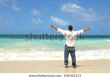 single male standing on beach facing ocean with arms wide open to the sky