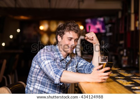 single man drinking beer at bar or pub, using his cellphone, texting or betting