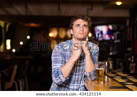 single man drinking beer at bar or pub, watching the game