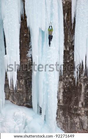 Single man ice climbing a frozen waterfall - stock photo