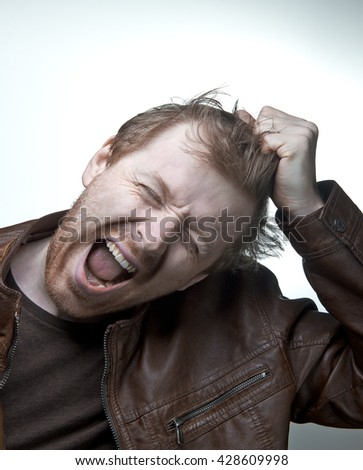 Single man  in a leather jacket tearing hair and screaming