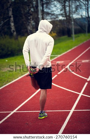 Single man in a sweatshirt stretching before run - stock photo