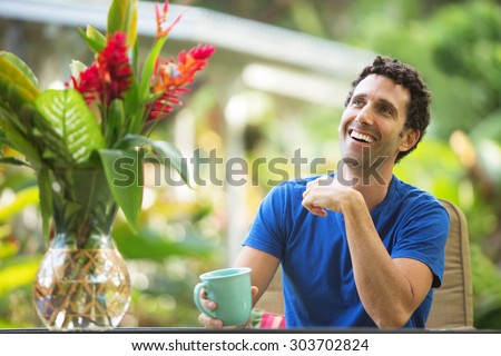 Single man with mug smiling looking up - stock photo