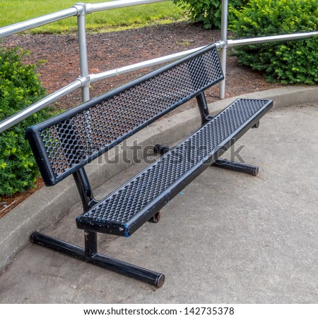 Single metal and black plastic coated park bench with aluminum fence in background