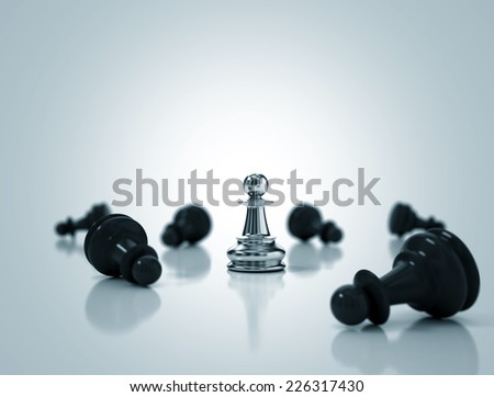 Single metallic pawn surrounded by a number of fallen black chess pieces - stock photo